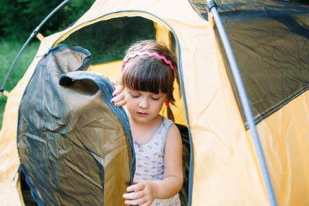 getting out: Little girl getting out of tent in forest. Young girl-scout studying camping lifestyle.