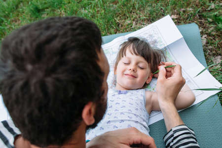 family tickle: Father tickling daughter with grass, enjoying rest outdoor. Happy family pastime