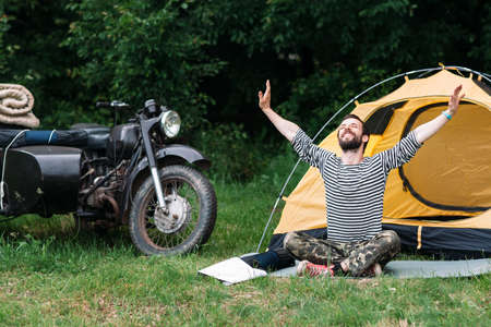 sidecar: Happy man taking sunbath in forest near the camping and motorcycle with sidecar. Relaxation, yoga practicing, unity with nature concept.