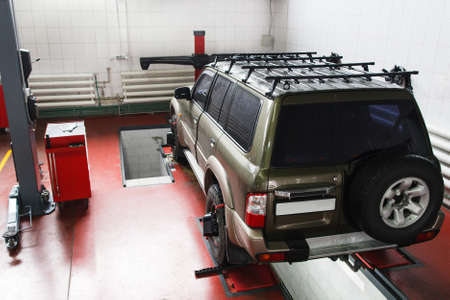 aligning: SUV on scheduled scanning at auto service. Professional car maintenance at modern repair shop