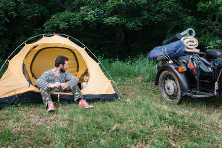 discovering: Family trip, child discovering the world. Interesting travel on sidecar in wild nature with dad, camping in forest Stock Photo