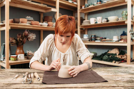 sculpting: Workshop of craftsman pottery, clay pot decorating. Intently drawing female potter on new jar. Stock Photo
