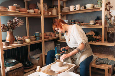 carefully: Pottery drying with special dryer. Carefully working young female potter. Small business of woman Stock Photo
