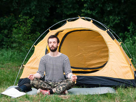 unworried: Young man practicing yoga in meditation pose, camping background.