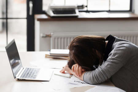 Sad fired crying female secretary. Dismissed office manager woman lying on her workplace desk in desperation