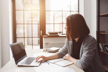 surfing the net: Beautiful woman surfing net at office on laptop. Uninteresting work, free time, break Stock Photo
