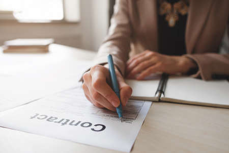 profitable: Female hand with pen completing personal information on form. Business woman signing profitable contract.