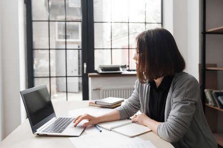 cansancio: Oficinista aburrido en el escritorio mirando la pantalla del ordenador. trabajo poco interesante aburrido, concepto cansancio Foto de archivo