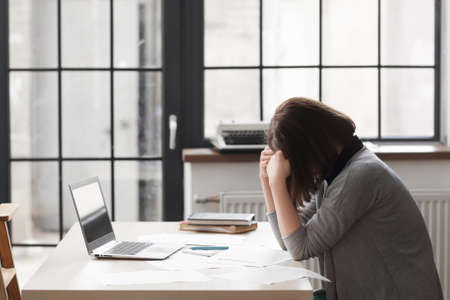 overworking: Tired business woman at workplace in office, holding her head in hands. Overworking, making mistake, stress, depression concept Stock Photo