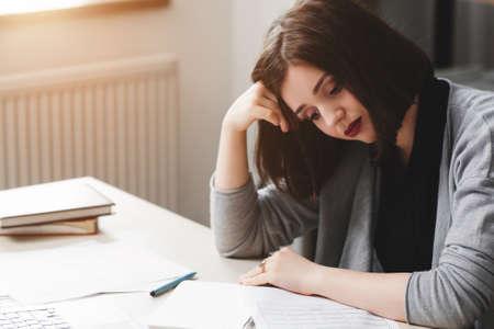 オフィス デスクで座っている作家のブロックを持つ若い女性。インスピレーションの欠如、絶望、創造的な危機概念 写真素材
