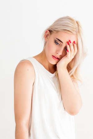 cansancio: atractiva mujer rubia con dolor de cabeza. La hembra joven puso la palma sobre su cabeza. La migraña, cansancio, frustración concepto