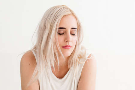 misunderstanding: Upset woman with eyes closed. Concept of misunderstanding, loneliness, frustration, failure, loss. Attractive blonde on white background Stock Photo