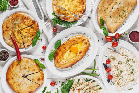 Banquet in georgian traditional style. Bakery products of national cuisine of Georgia: khachapuri, cheburek, lavash, meat pies.