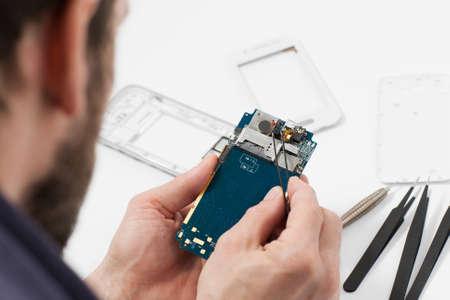 pinzas: Reparador desmontar teléfono inteligente con pinzas.