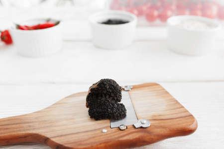 truffe blanche: Champignon de la truffe sur râpe sur blanc fond en bois