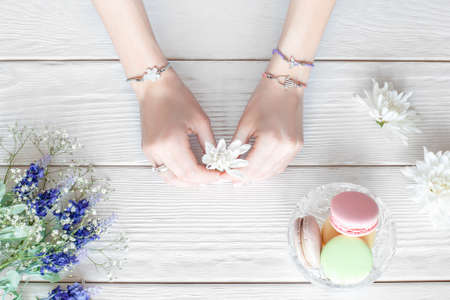 Hands of female florist holding flowers for creating bouquet on white wooden table, flat lay.