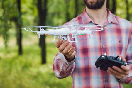 L'homme non reconnaissable courir drone avec la caméra dans la forêt. Examen de la nouvelle antenne quadrocopters extérieur sans pilote. outil moderne pour photo et vidéo aérienne Banque d'images - 61529164