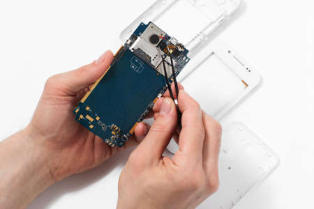 disassembly: Repairman disassembling smartphone with tweezers. Stock Photo