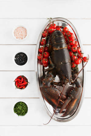 raw lobster: Big raw lobster in plate on table before cooking, flat lay. Stock Photo
