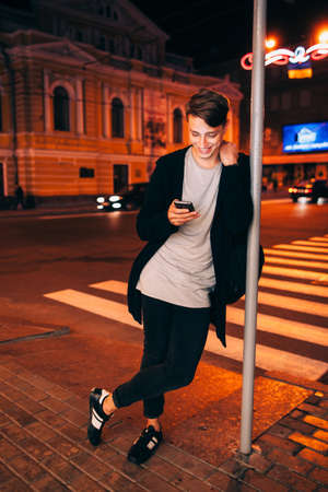 lamp post: Smiling guy with smartphone in night city. Young handsome man standing near lamp post and reading something on his phone in evening street Stock Photo