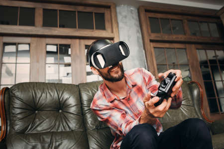 adult entertainment: Young man playing video games in virtual reality headset. Male adult with joystick and vr glasses controlling vehicle while playing. Modern technology, innovation, cyberspace, entertainment concept