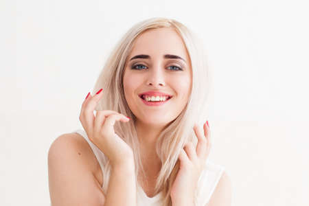 talkative: Talk-active blonde gesturing her speech. Portrait of young beautiful laughing woman with raised hands, white background Stock Photo