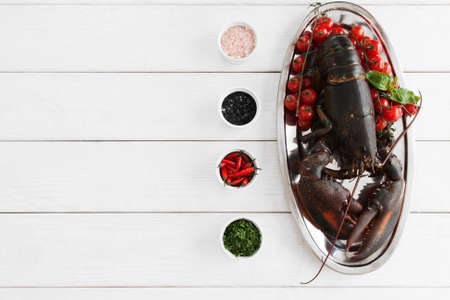 raw lobster: Big raw lobster in plate on table before cooking, flat lay. Seafood preparing by original recipe, mediterranean cuisine, uncooked crayfish on white wooden background, copy space