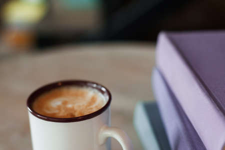Cup of coffee with purple folders, free space. Working in office, coffee-break at workplace.