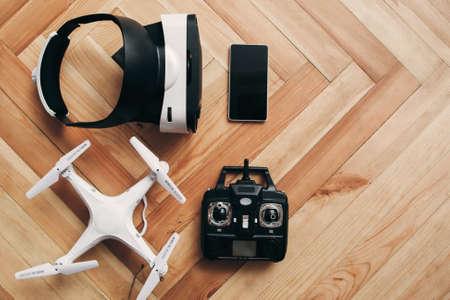 가상 현실 안경 및 무인 항공기, 여유 공간, 평면 배치. 원격 제어와 vr 헤드셋 복사본 공간 목조 배경에 스마트 폰 quadrocopter에 상위 뷰.