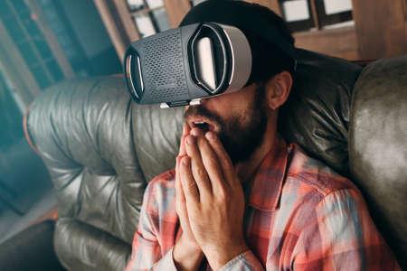 Homme choqué avec des lunettes de réalité virtuelle. Male regarder une vidéo passionnante dans le casque vr, technologie 3d impressionnante. Cinéma à la maison, innovation, cyberespace, concept de divertissement Banque d'images - 62995639