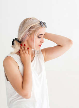 sensitive: Beautiful sensitive woman touching her neck. Side view of young attractive blonde in sunglasses, white background