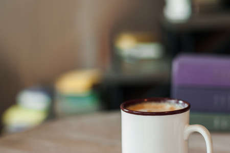 Cup of cappuccino on blurred office background. Fresh tasty beverage in ceramic mug, coffee break concept, free space Stock Photo