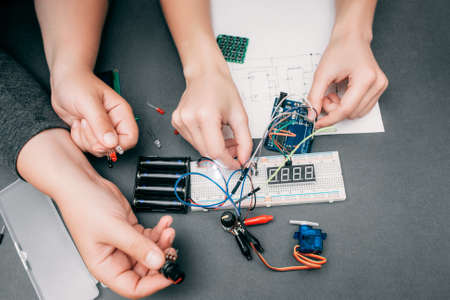 delineation: Hands of engineers connecting electronic components. Workplace of electrician working with modern technologies, creation of engineering construction