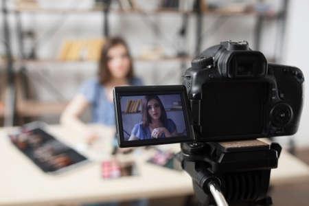 Jeune beauté blogueuse sur l'écran de la caméra. Belle fille enregistrement vidéo en studio. Mode, maquillage, concept technologique
