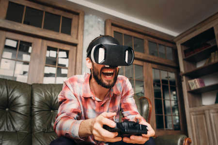 adult entertainment: Excited man playing video game in vr glasses with joystick. 3d virtual headset impressed male adult. Modern technology, innovation, cyberspace, entertainment, gaming concept Stock Photo