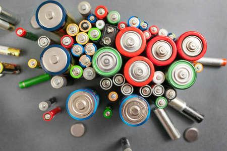 Selectie van verschillende batterijen, bovenaanzicht op kleurrijke commerciële accumulators op grijze achtergrond. Creatieve energiesamenstelling. Ecologie concept Stockfoto