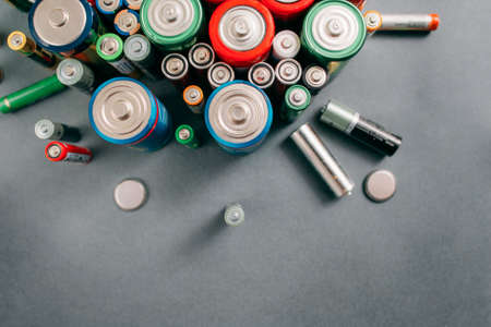 free space: Top view on portable batteries on gray background, free space. Colorful energy composition, variety of different kinds of accumulators, copy space