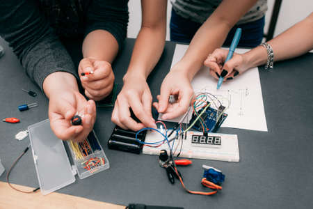 delineation: Collective electronics development with scheme. Breadboard and components with engineers hands on table, teamwork concept