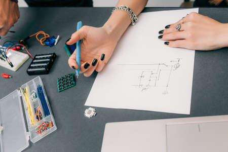 delineation: Female engineer drawing scheme of electronic construction. Woman hands designing engineering construction on paper, electrical components on table Stock Photo