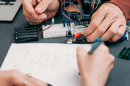 recap: Woman recapping electronics creation process. Engineer assistant drawing wiring diagram of electronic construction. Modern technologies, innovation, diy laboratory Stock Photo