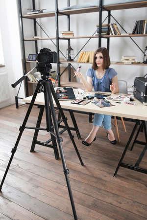Ung söt bloggare spelar in video på kamera. Modern ockupation, kvinna som berättar om smink kosmetika i hennes vlog