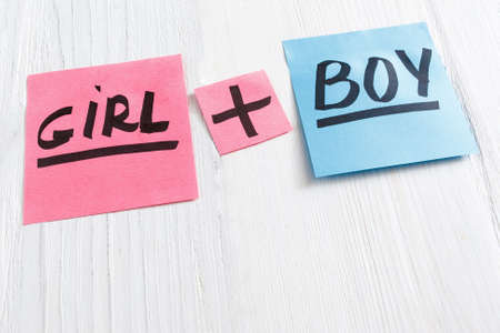 text free space: Pink and blue stickers with girl plus boy text, copy space. Three colorful sheets of paper on white wooden background, free space. Its a girl and boy twins concept Stock Photo