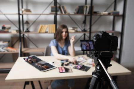 自宅で女性のビデオブロガー記録ビデオ。若いブロガーの顔画像と、カメラ画面のクローズ アップ。ファッション、美容、技術の概念