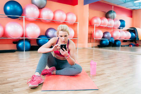 net surfing: Athlete blonde using smartphone at gym. Attractive female fitness trainer surfing net while having rest between trainings. Healthy lifestyle, technologies in life concept Stock Photo
