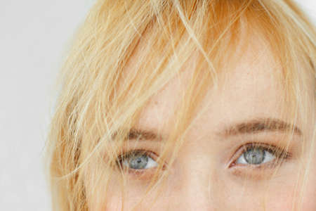 carroty: Beautiful gray eyes of red-haired woman close-up. Half face portrait of attractive carroty girl with light smiling peepers and freckles. Stock Photo