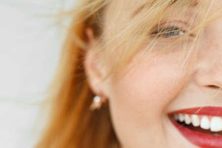 carroty: Half face of laughing red-haired woman. Close-up portrait of sunny adorable carroty girl with freckles. Blurry live dynamic photo, free space Stock Photo