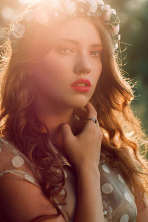 wise woman: Beautiful girl in wreath touching her neck, sunset light and forest background. Healthcare, alternative medicine, medicinal herbs, witch, wise woman concept Stock Photo