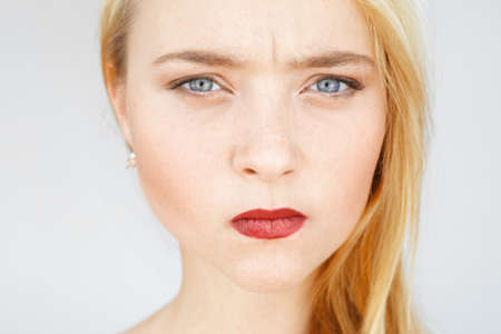 Angry sad red-haired woman portrait. Young female with very serious and blaming look, pursed lips. Angry, frowning, grumpy carroty girl close-up. Stock Photo
