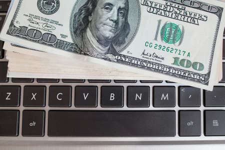 batch: Batch of one hundred dollar bills on keyboard, close-up. American money banknote on laptop. Income through internet, programming concept Stock Photo