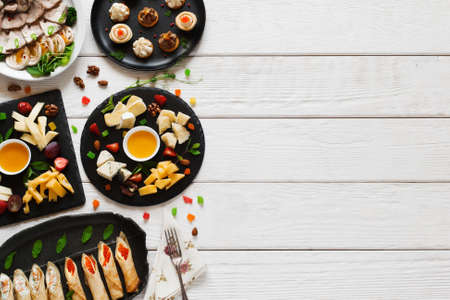 text free space: Tasty snacks on white wooden table, free space. Variety of light appetizing luxury gourmet meals in right side of picture with copy space for text